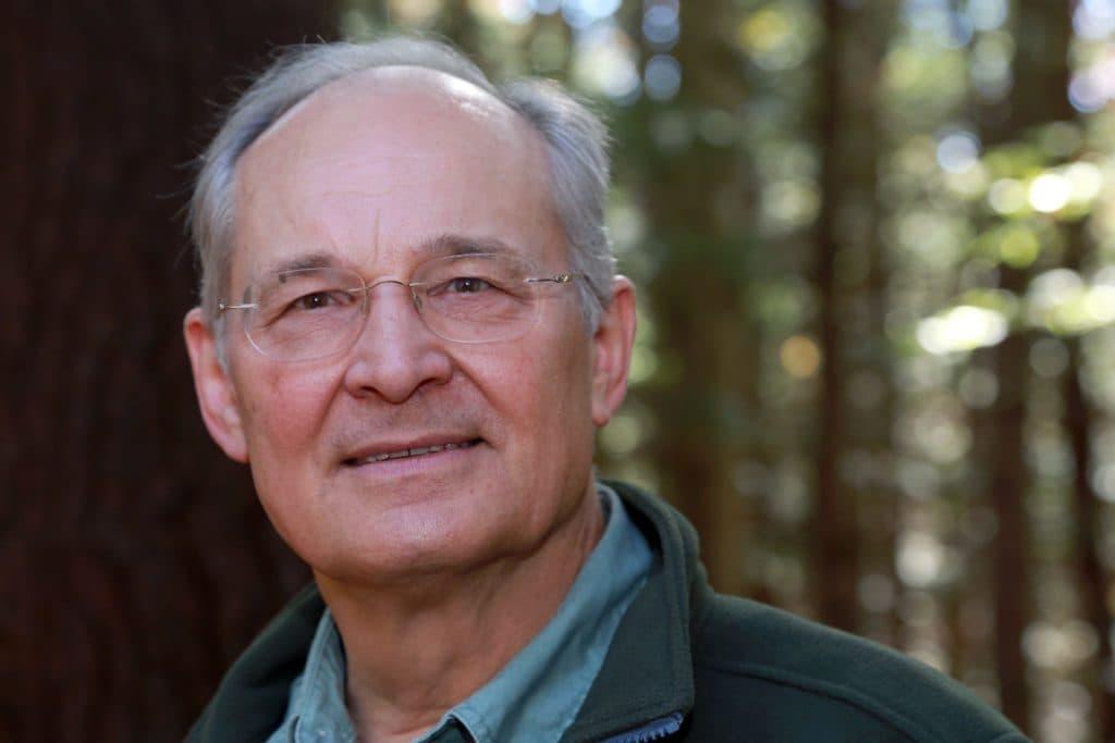 medium closeup of Jan Krzywicki standing in front of trees in soft focus