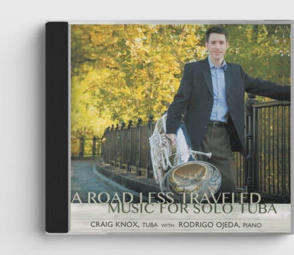 CD cover for Connections CD, shows tuba player Craig Knox leaning against a fence holding tuba